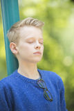 Relaxed happy teenager boy outdoor. Portrait thoughtful and relaxed young blond teenage boy outdoor with closed eyes, concentrated and meditating, with blurred Stock Image