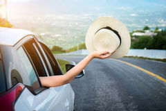 Relaxed happy traveler, Young beatiful asian gilr holding hat we. Ave and Reach out of the car at sunset and beautiful view with mountain road background stock photo