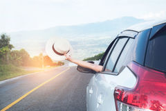 Relaxed happy traveler, Young beatiful asian gilr holding white. Hat weave and Reach out of the car at sunset and beautiful view with mountain road background stock images