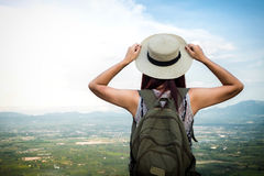 Relaxed happy traveler, Young Hipster woman traveler with backpack holding hat weave and looking at beautiful view nature royalty free stock image
