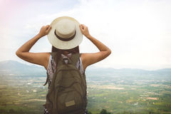 Relaxed happy traveler, Young Hipster woman traveler with backpack holding hat weave and looking at beautiful view nature stock images