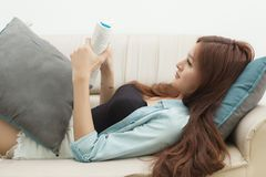 Relaxed happy woman reading a book in an ebook reader sitting on a couch at home Stock Image
