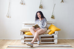 Relaxed happy woman reading a book sitting on a couch at home Stock Photos