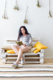 Relaxed happy woman reading a book sitting on a couch at home Stock Images