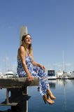 Relaxed and Happy Woman sitting at Marina. An attractive looking mature woman is sitting at the end of a wooden boardwalk over the calm water of a marina, with Royalty Free Stock Photos