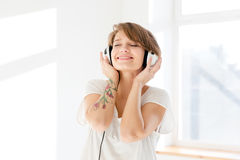 Relaxed happy young woman listening to music using earphones Stock Photo