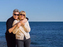 Relaxed healthy couple enjoying the coast. Posing in front of a calm blue sea in a loving embrace smiling at the camera with copyspace to the right Royalty Free Stock Photo