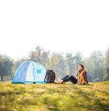 Relaxed hiker sitting next to a blue tent Stock Images