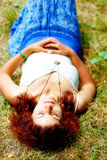 Relaxed hippie girl lying on meadow on bright midsommer day. Stock Photo