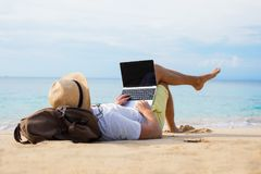 Relaxed man with laptop on the beach. Relaxed hipster man using laptop while lying on the beach Stock Photography
