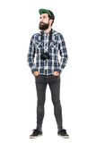 Relaxed hipster wearing black dslr camera over neck with hands in pockets. Full body length portrait isolated over white studio background Royalty Free Stock Photos