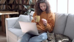 Relaxed hispanic teen girl using laptop watching movie playing with cat on sofa.