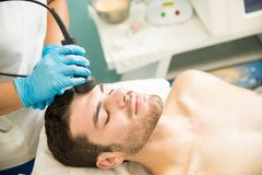 Cellular facial therapy in a spa. Relaxed Hispanic young men getting cellular and rejuvenation facial therapy in a spa Stock Images