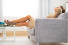 Relaxed housewife laying on divan in living room. Relaxed young housewife laying on divan in living room Stock Images
