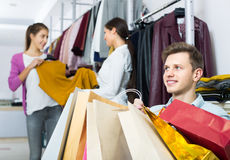 Relaxed husband sitting with purchases. Wife 25s buying more clothes Royalty Free Stock Photo