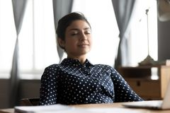 Free Relaxed Indian Young Woman Rest Sit At Desk Eyes Closed Royalty Free Stock Image - 168423666