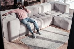 Relaxed international male person sitting on sofa. Talk to me. Delighted brunette man expressing positivity while talking per telephone stock photos