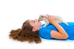 Relaxed kid girl kissing puppy chihuahua dog lying Royalty Free Stock Photos