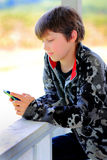 Relaxed Kid Texting. Relaxed happy young boy with dark hair wearing a camouflage jacket leaning against a deck railing texting on a phone. Shallow depth of field Stock Photo