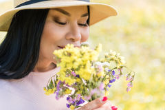 Relaxed lady enjoying scent of wildflowers. Portrait of happy asian woman smelling wild flowers on meadow. Her eyes are closed with pleasure. Copy space stock image