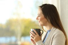 Relaxed lady holding coffee cup looks outside at home. Relaxed lady holding coffee cup looks outside through a window at home stock image
