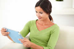 Relaxed lady looking at a tablet Royalty Free Stock Images