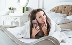 Relaxed Lady Lying In Bed And Talking On The Phone Stock Photos