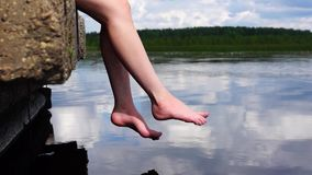 Relaxed legs sways over water stock video footage