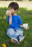 Relaxed little boy eating cotton candy at park. Full length of a relaxed little boy eating cotton candy at the park Stock Photography