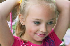Relaxed Little Girl. A relaxed contented little blond girl in pink blouse, bow in her hair. Shallow depth of field Royalty Free Stock Image