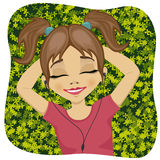 Relaxed little girl lying on grass listening to music outdoors with eyes closed Royalty Free Stock Photo