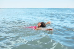 Relaxed little girl in swimsuit lying on her back, swimming in deep sea, enjoying landscapes, looking at sky, feeling relaxation, Royalty Free Stock Photos