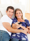 Relaxed lovers watching television lying on sofa Stock Photos