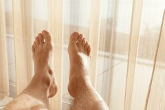 Relaxed male feet lay near wide window. Relaxed male feet lay in sunlight near wide window with tulle Royalty Free Stock Images