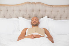 Relaxed man with book lying in bed Royalty Free Stock Photos