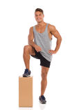 Relaxed Man With A Box. Smiling young man in black shorts and sneakers standing close to a cardboard box and holding one leg on it. Full length studio shot Stock Photography