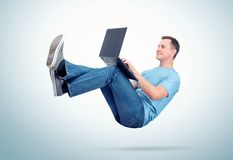 Relaxed man in casual clothes working on a laptop soaring in the air. Unreal concept comfort.  stock photo