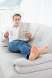 Relaxed man with coffee cup while reading newspaper on sofa Stock Photos