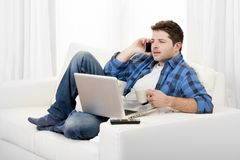 Relaxed man with computer talking on mobile. Young attractive relaxed man with computer talking on mobile cell phone Royalty Free Stock Photos