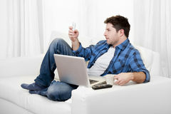 Relaxed man with computer writting text on mobile. Young attractive relaxed man with computer writting text on mobile cell phone Stock Photos