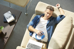 Relaxed man on couch with laptop Royalty Free Stock Photos