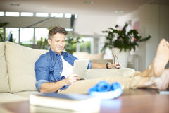 Relaxed man with digital tablet Stock Photo