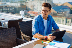 Relaxed man dreaming while using tablet computer. Dreaming big. Cheerful young guy in casual looking at something with a smile on his face while sitting at a royalty free stock photo