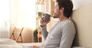 Man drinking coffee in bed. Relaxed man drinking morning coffee in bed stock video footage