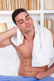 Relaxed man drying hair with white towel. Sitting in front of book shelf Stock Photo