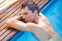 Relaxed man at edge of swimming. Relaxed young man resting at edge of swimming pool Royalty Free Stock Photos