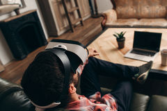 Relaxed man enjoying virtual reality glasses. At home. Guy having rest in vr headset in front of laptop, back view. Modern technology, innovation, cyberspace royalty free stock photos