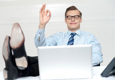 Relaxed man with excellent gesture. Looking at laptop Stock Image