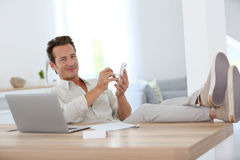 Relaxed man with feet on table working at home Stock Image