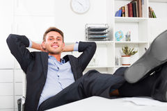 Relaxed man with feet up on desk Royalty Free Stock Images
